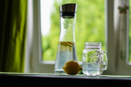 A safe alternative to drinking essential oils: a glass with water and sliced lemons